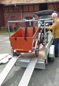 Ein dreirädriges Lastenrad mit großen Transportkasten vorn wird von einem Anhänger mit Schienen auf den Erdboden befördert.
