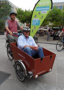Ein Mann mit Fahrradhelm steuert ein Lastenrad mit großer Transportbox vorn, in der ein älterer Herr mit Fahrradhelm als Passagier sitzt. Im Hintergrund ist ein Beachflag von Verkehrswende Fulda (VCD) zu sehen.